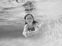 a child in goggles swimming under water