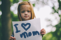 """""""I love Mom"""" sign held by a child."""