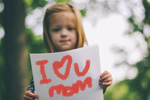 girl holding I love you mom sign