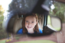 smiling face of a girl child in a rearview mirror