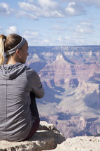 woman sitting at the top of a canyon
