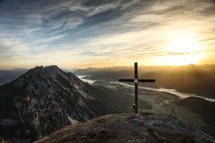 cross on a mountain top at sunrise