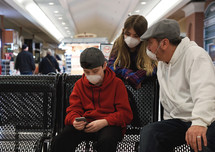 A family is sitting on a bench at a mall wearing virus protection masks. One person is looking on their phone for information.