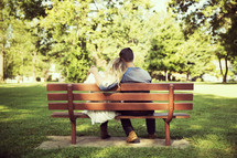 a couple snuggling on a park bench