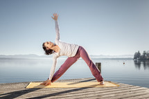 woman stretching and doing yoga on a dock