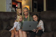 a mother looking at a computer screen with her daughters