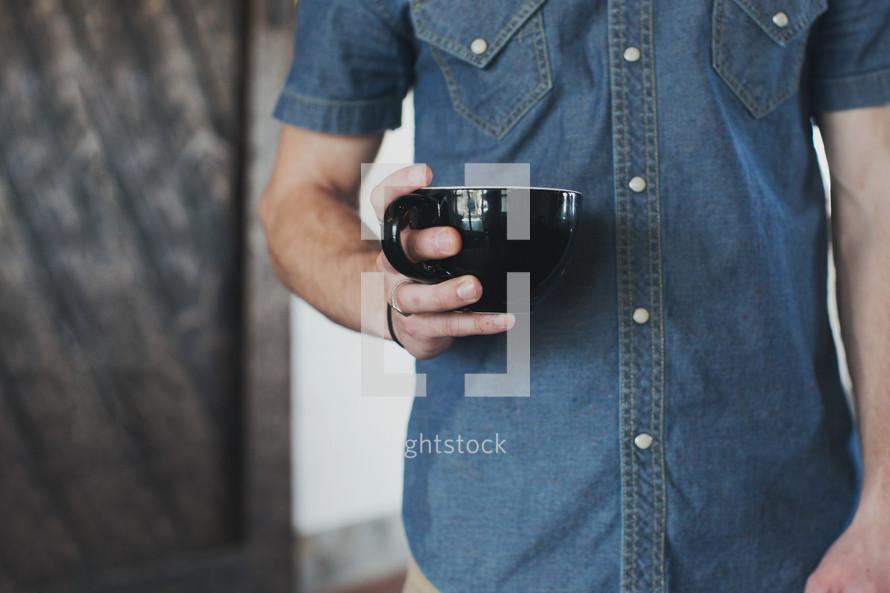 torso of a man holding a mug