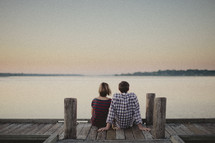 A couple sitting on a dock looking out at the water