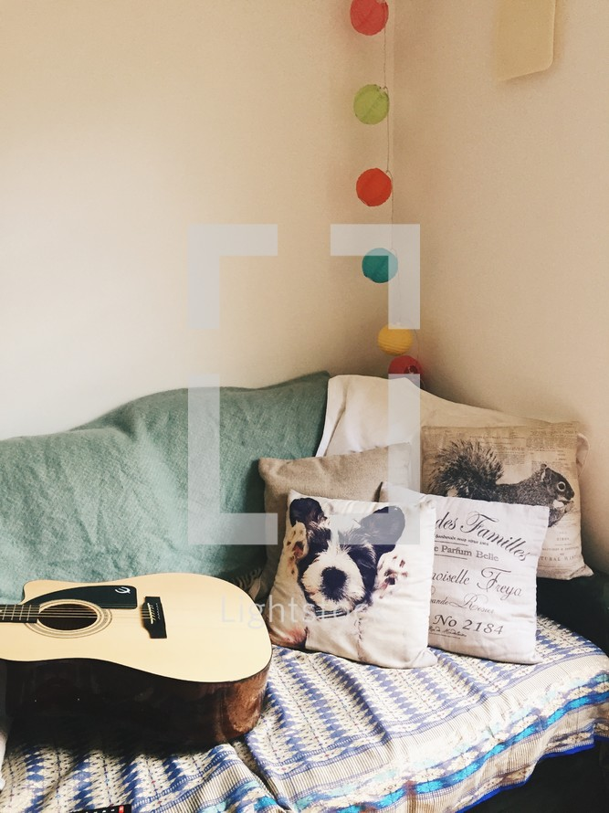 throw pillows and acoustic guitar on a couch