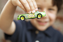 A little boy holds a toy car in front of his face