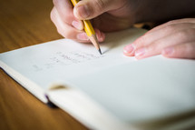 A hand writing the fruit of the spirit into a journal with a pencil.