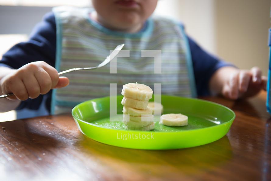 toddler eating sliced bananas