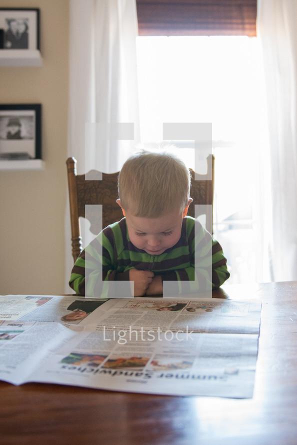 toddler boy reading a newspaper