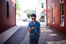 man standing in an alley listening to an iPod
