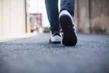 man's shoes walking on a street