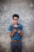 a man reading a Bible standing in front of a gray wall with graffiti
