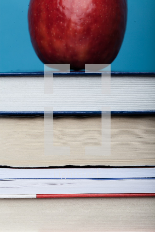 A red apple on a stack of books.