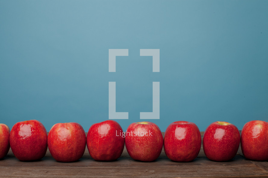 A line of red apples on a wooden surface with a blue background.