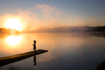 a girl on a pier over a steaming lake at sunrise