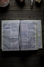 notes on the pages of a Bible on a workbench
