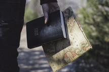 man holding a Bible and world map