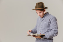 man in a hat reading a Bible