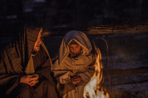 A man and child dressed in Biblical clothing sit near a fire.