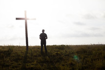 a man praying in front of a cross