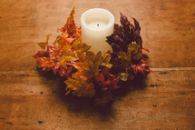 Candle with a wreath of fall leaves on a wooden table -- Thanksgiving decor.