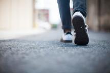 sneakers walking on a sidewalk