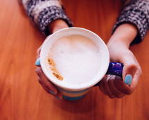 A woman's hands holding a cup of cappuccino.