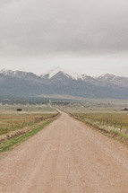 Dirt road leading to the snow-covered mountains.