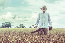 a farmer with a blade and a bible in a wheat field