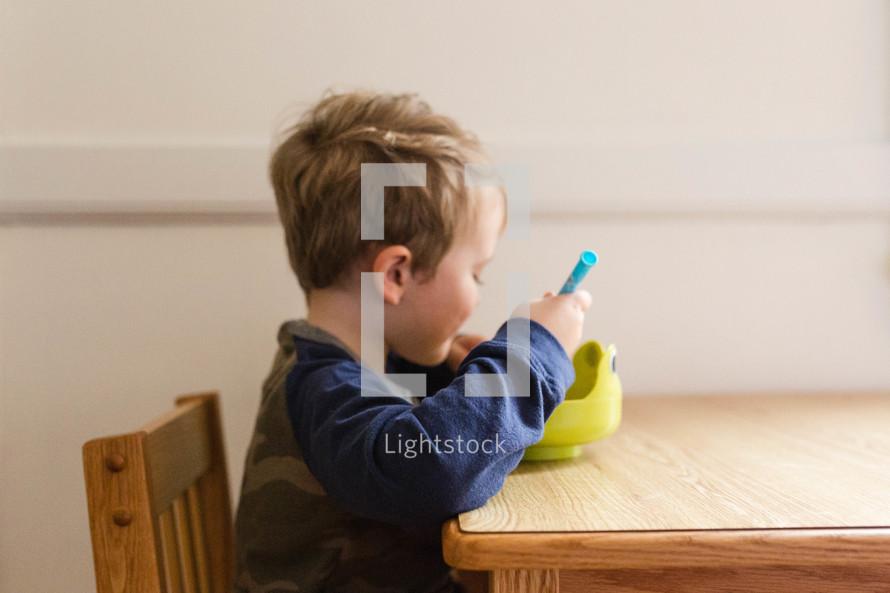 toddler boy eating cereal