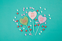 Small candy hearts surrounding Valentine candy hearts with Valentine messages.