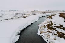 snow along a winter stream