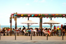 A crowd eats on the patio near the beach in Barcelona
