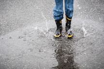 child splashing in a puddle