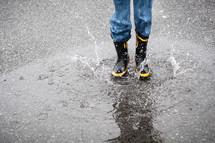 child splashing in a puddle