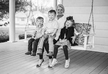 grandmother on a porch swing with her grandchildren