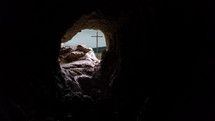 The cross is visible through the opening of a rocky cave in the mountain.