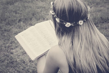 a girl with flowers in her hair reading a Bible