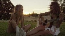 Girl Plays Guitar Outside with Friend in Slow Motion