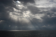 Sun beaming through the storm clouds over ocean after the storm