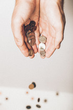 cupped hands pouring out coins