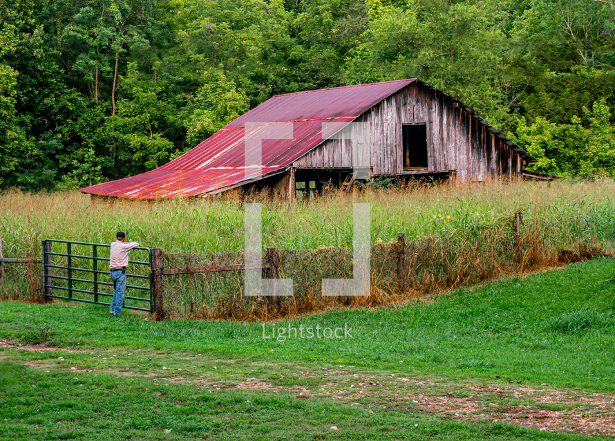 a farmer looking at an old barn