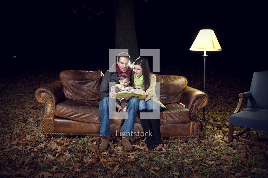 family reading sitting on a couch outdoors