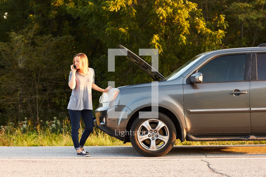 woman standing next to a vehicle broken down on the side of the road