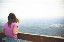 a woman looking over a railing at mountains below