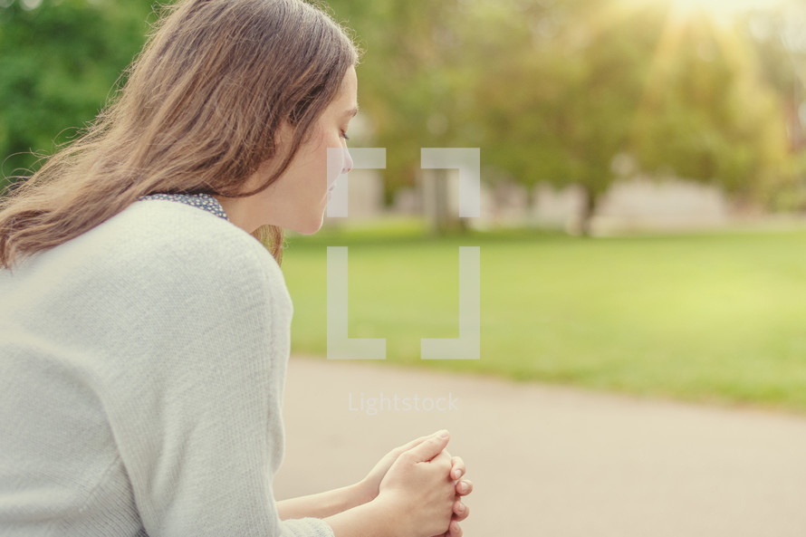 Christian worship and praise. A young woman is sitting and praying on a park bench